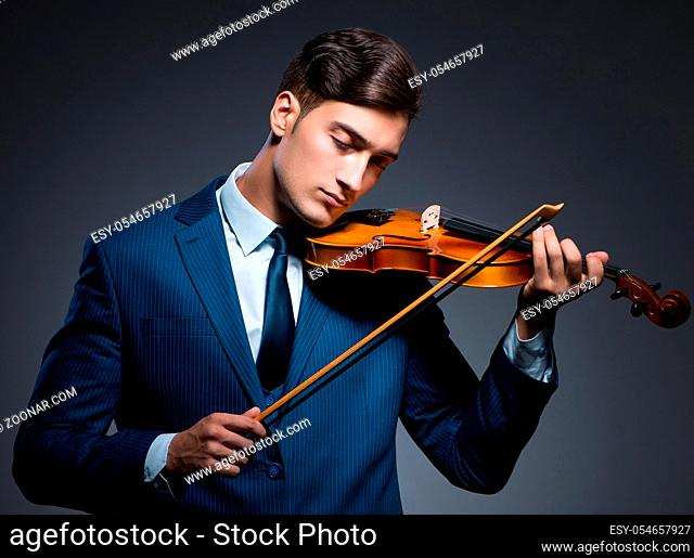The young man playing violin in dark room