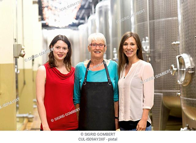 Portrait of three women in wine cellar, smiling
