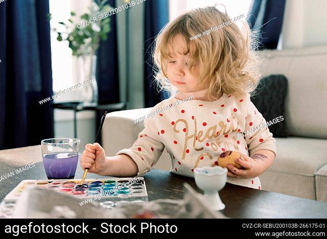 Little toddler girl painting eggs with watercolors for Easter