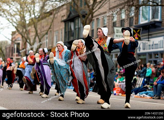 Holland, Michigan, USA - May 11, 2019: Tulip Time Festival, Young women wearing traditional Dutch Clothing dancing in the streets of Holland