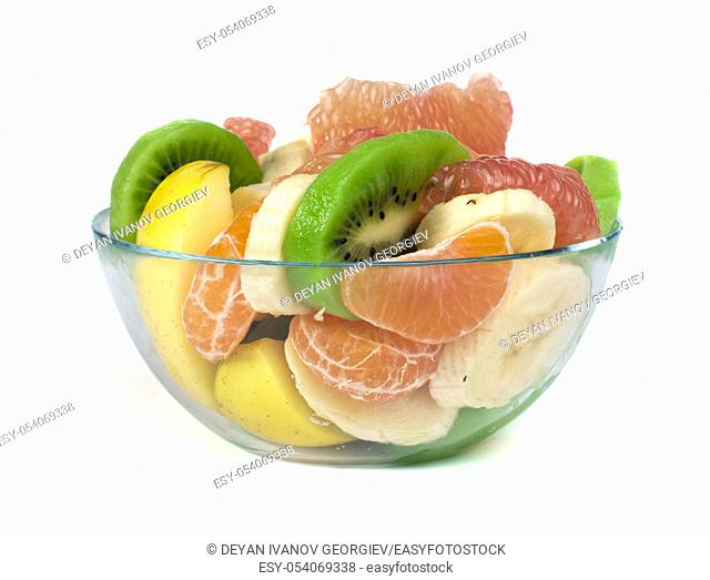 Fruit salad with citrus in a glass bowl on a white background