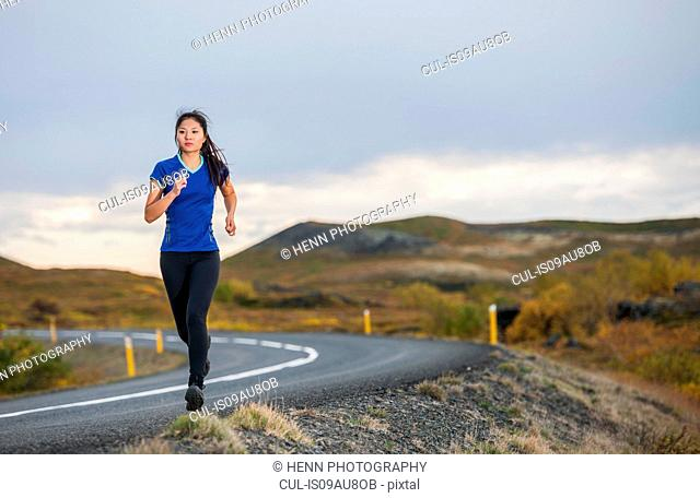 Mid adult woman running on road in rural landscape