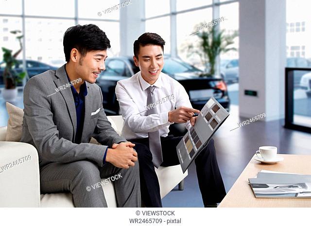 Car dealer with customer in showroom