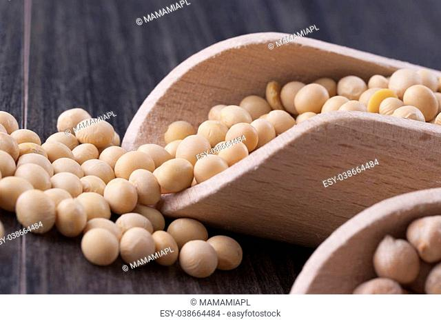 Close up photo of a raw food - yellow beans - soybeans placed on a dark wooden background