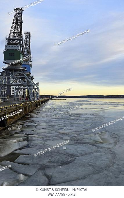 Ice floes are floating on a harbor bay in winter