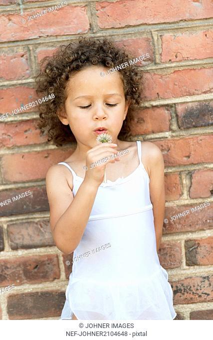 Girl blowing dandelion outside building