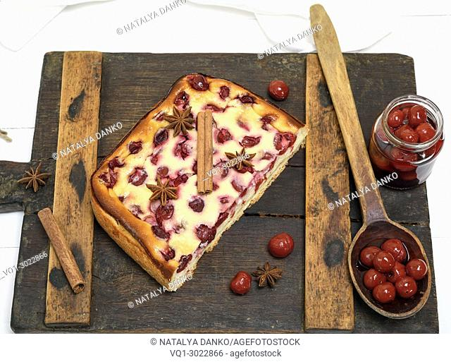 cottage cheese and cherry pie on a brown wooden board, top view