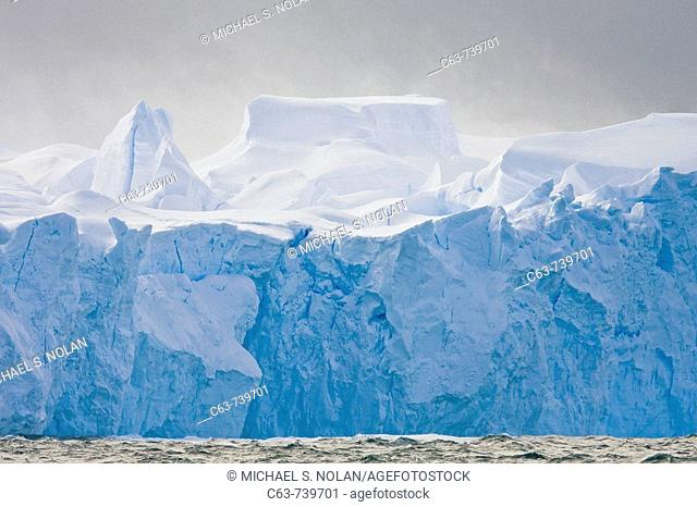 Fierce gale-force winds carving tabular icebergs below the Antarctic Circle around the Antarctic Peninsula during the summer months  More icebergs are being...