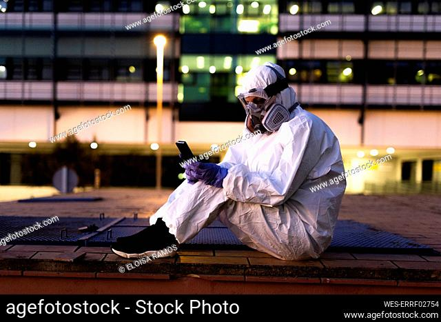 Female scientist wearing protective suit and mask using smartphone in front of a laboratory