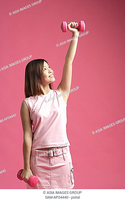 Woman dressed in pink, lifting dumbbell