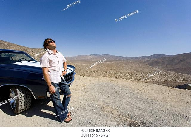 Young man in sunglasses leaning on car in desert, looking up