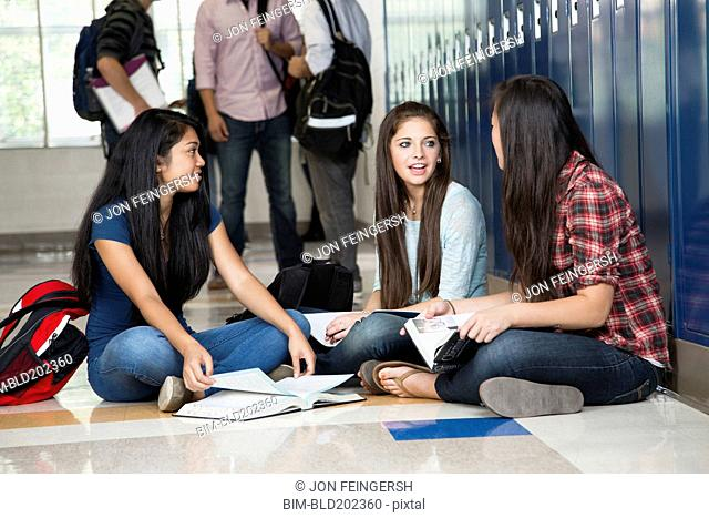 High school students sitting in corridor together