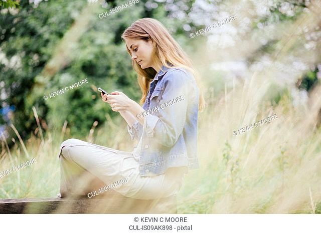 Young woman reading texts on smartphone on park bench