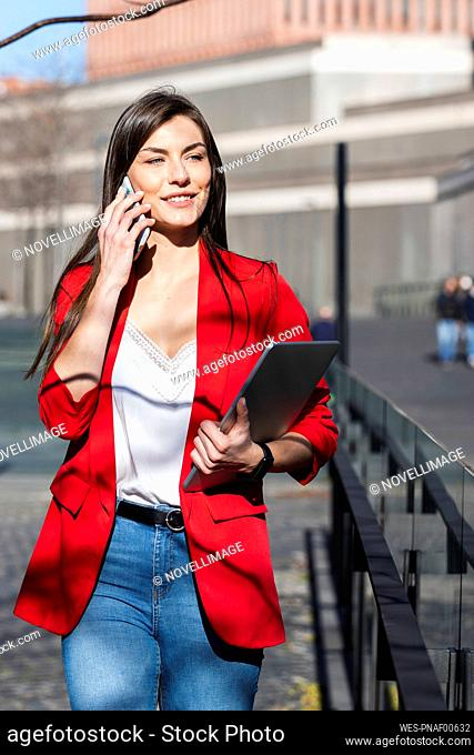 Smiling businesswoman with laptop talking on mobile phone while walking on footpath