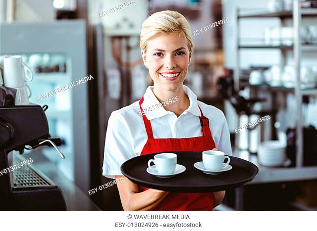 Pretty barista holding two cups of coffee
