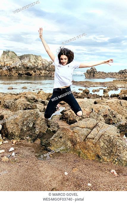 Vital brunette woman jumping on the beach