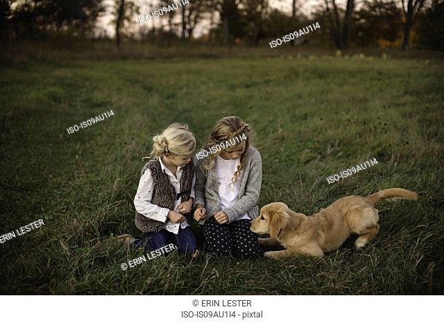 Two young girls sitting in field with pet dog