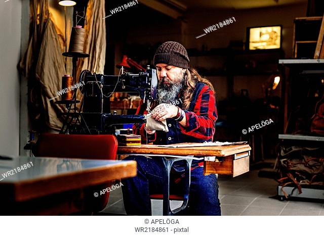 Worker sewing bag pocket at table in workshop