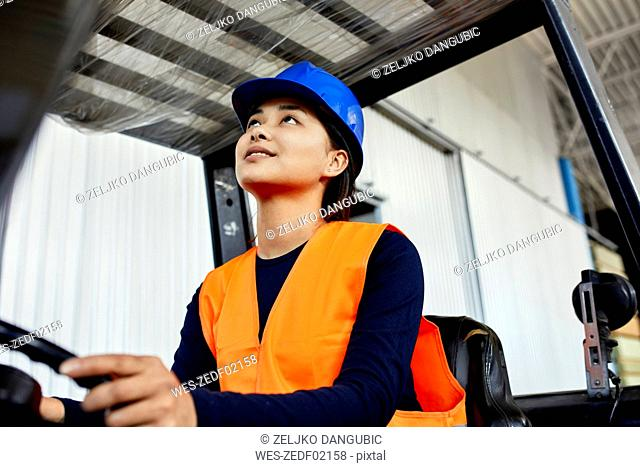 Female worker on forklift in factory looking up