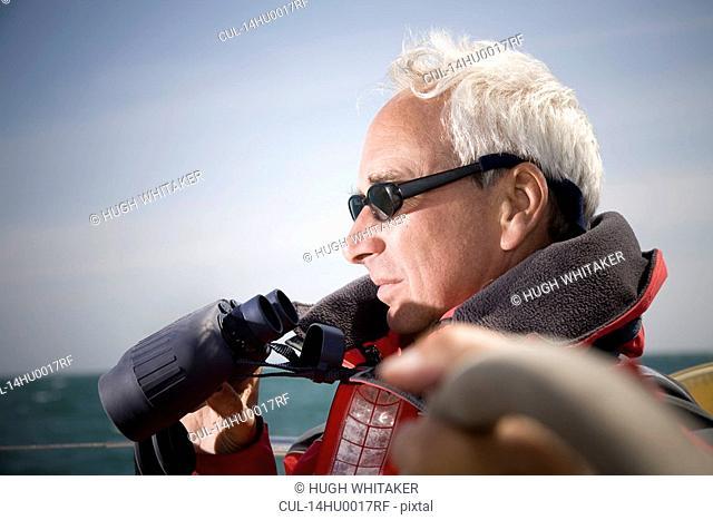 Man with binoculars sailing