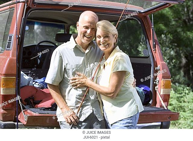 Senior couple standing beside parked SUV, arms around each other, man with fishing rod, smiling, portrait