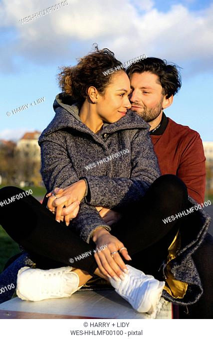 Smiling young couple sitting outdoors