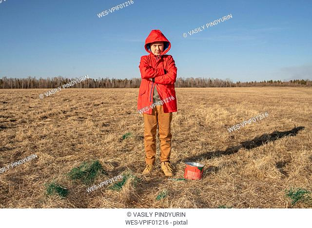 Serious boy with paint bucket in steppe landscape