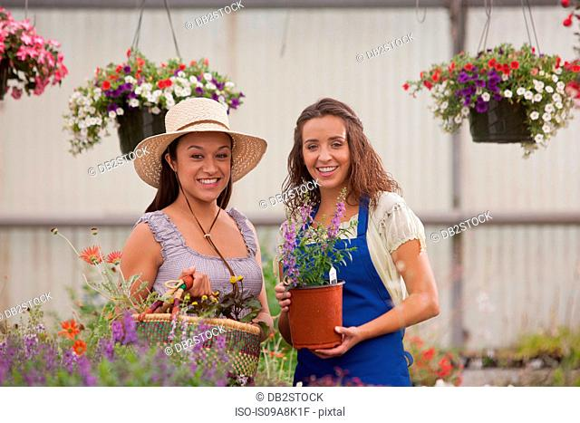 Young women holding plants in garden centre, smiling