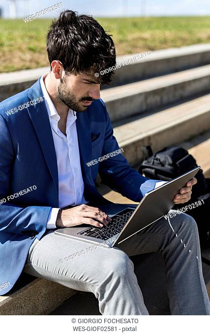 Young businessman sitting on stairs using laptop