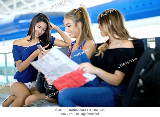 Group of 3 young women waiting at airport terminal