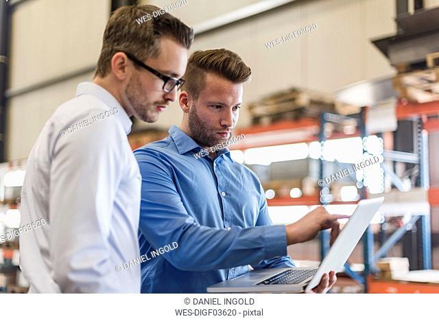 Two businessmen sharing laptop on factory shop floor