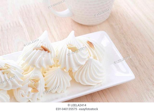 Meringue dessert placed in white dish on wooden table