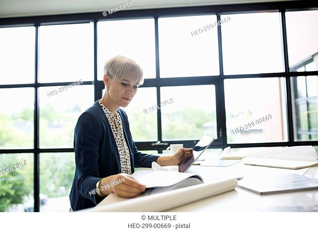 Female architect with blueprints using digital tablet at office table
