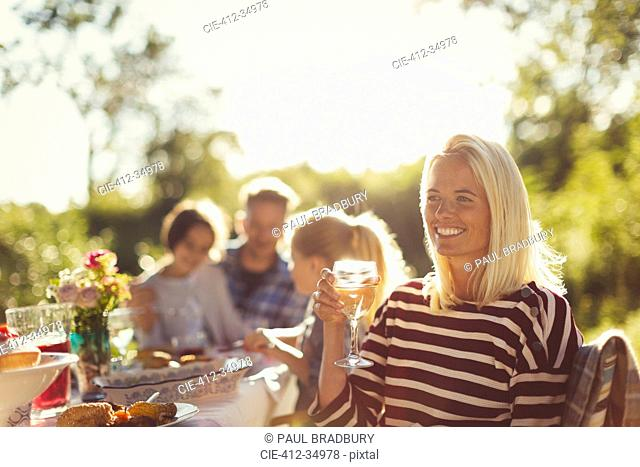 Smiling woman drinking wine at sunny garden party patio table