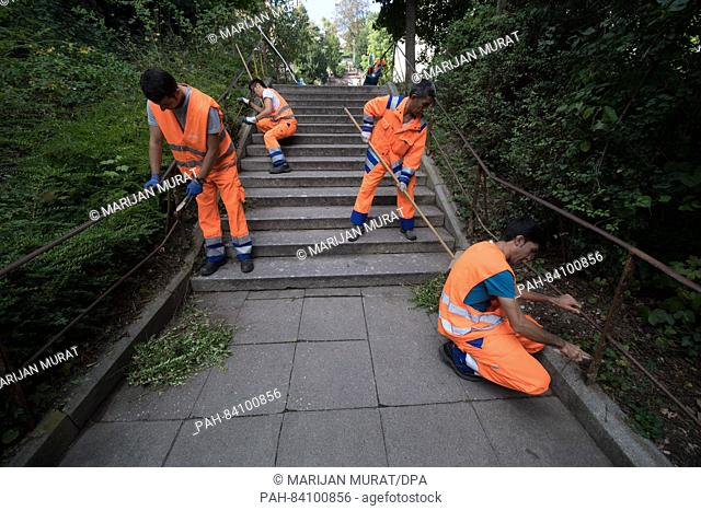 Refugees maintain steps including the banister in the context of a project by the city of Stuttart in Stuttgart, Germany, 21 September 2016