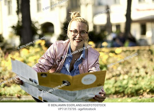 Woman with city guide map in park, in Berlin, Germany