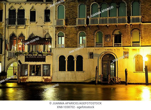 Night view of a Venetian canal with their facades in the water where you can see the terrace of a restaurant with people eating dinner in the moonlight