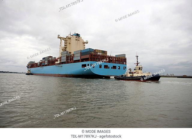 A container ship being escorted to port by tug boats, sea level