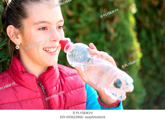 Beautiful girl is drinking water the hot sun in the park. Healthily concept. Healthy lifestyle concept. copy space. Portrait happy smiles beautiful girl