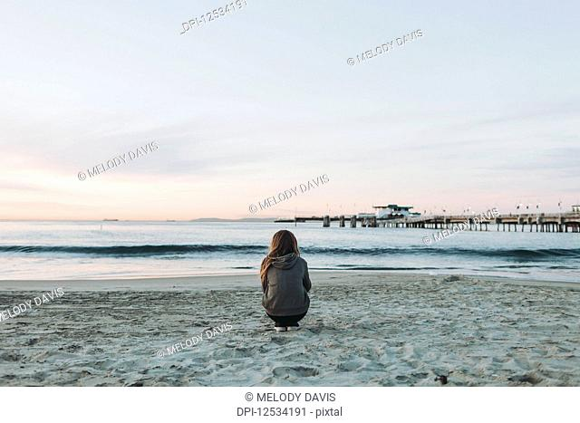 A girl crouches on the beach looking out over the ocean to the horizon at sunset; Long Beach, California, United States of America