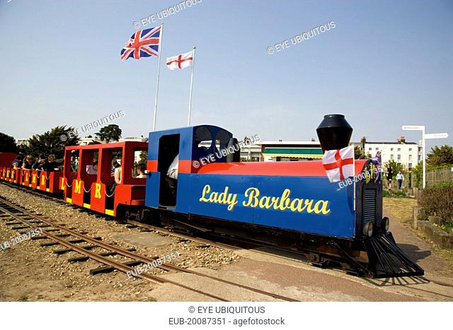 Families enjoying a miniature railway ride in Norfolk Gardens with Union Jack Flag flying behind