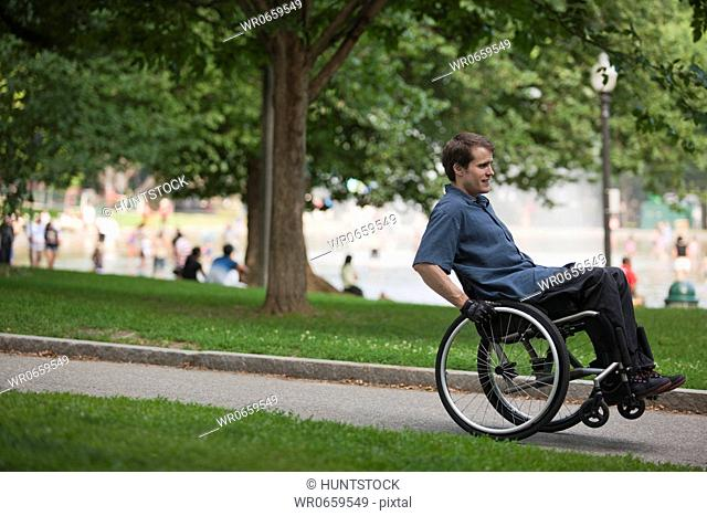 Man with spinal cord injury in a wheelchair on path in a public park
