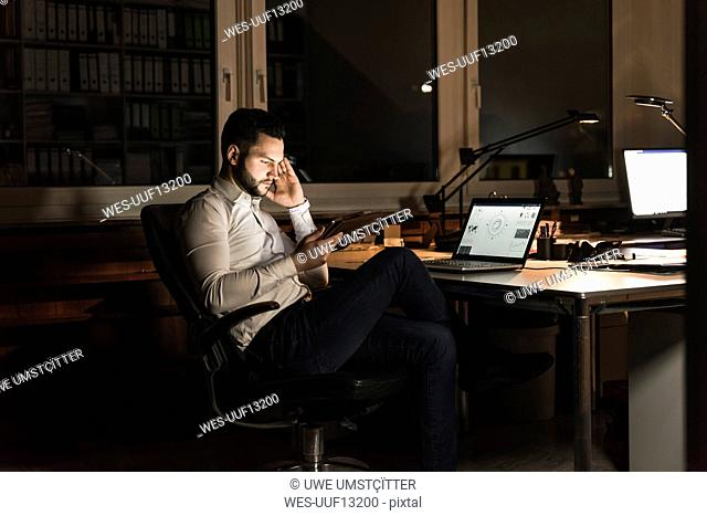 Businessman using tablet in office at night