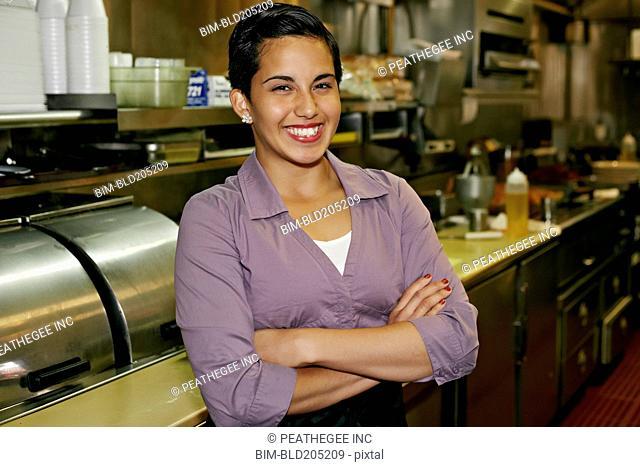 Hispanic waitress smiling in restaurant