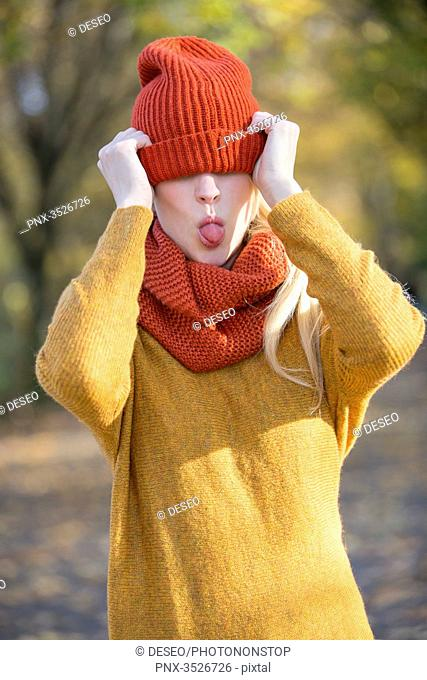Playful young woman covering her eyes with cap in park in autumn