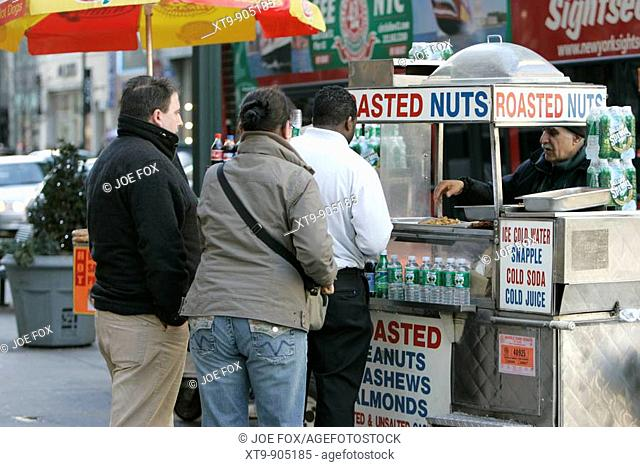 middle eastern origin street vendor selling roasted nuts and soft drinks to queue of mixed race people west 34th street outside empire state building