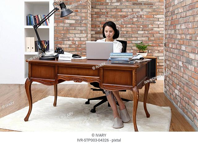 A young woman sitting at a desk with a computer