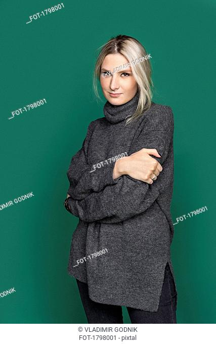 Portrait of woman with blond hair and wearing gray turtleneck sweater