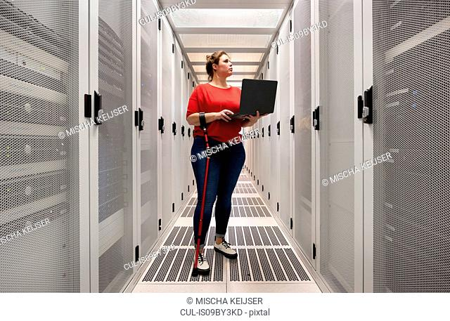 Woman with a damaged hip joint working in data centre