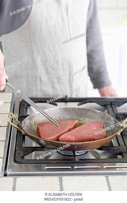 Man frying tuna steaks in pan
